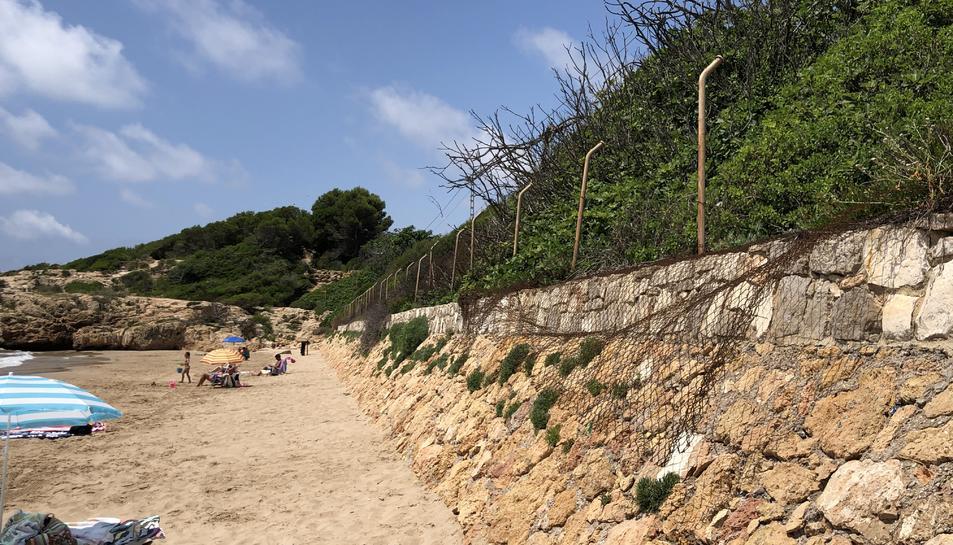 Imatge del mal estat en què es troba la tanca que separa la via del tren de la platja Llarga, molt estreta per les crescudes del mar.
