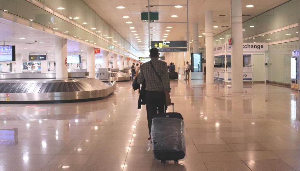 Un viatger caminant amb maletes a la zona d'arribades de la T1 a l'aeroport del Prat el 19 de juny del 2020.