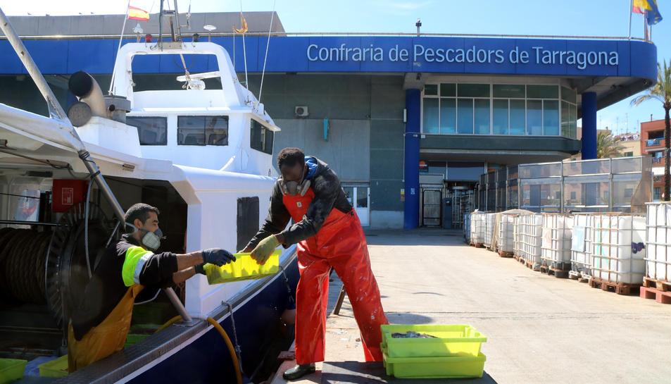 Ds pescadors començant a descarregar caixes de peix d'una barca d'arrossegament.