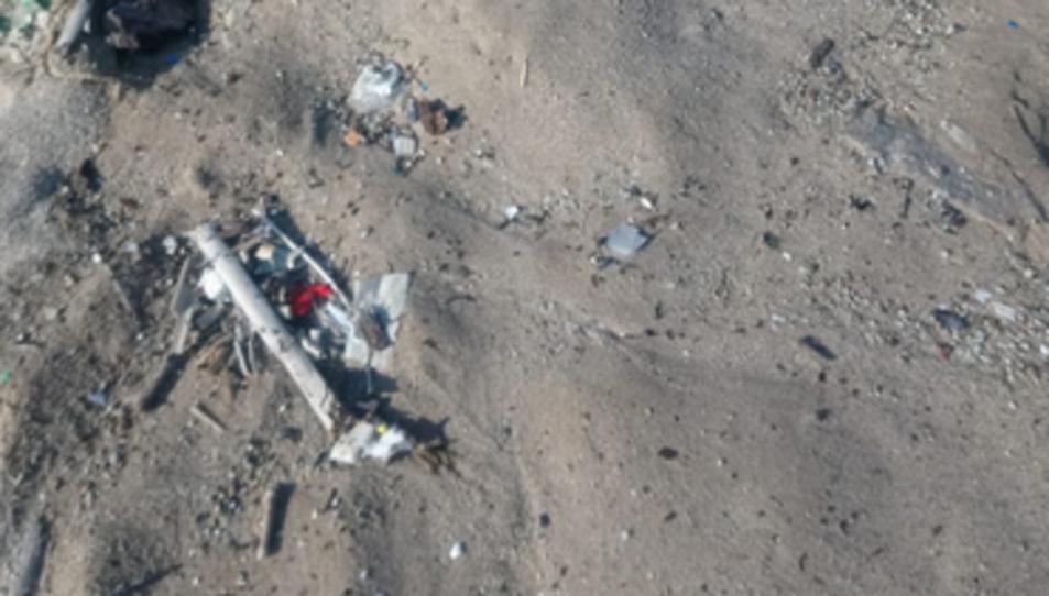 Detalls de brutícia a l'arena de la platja.