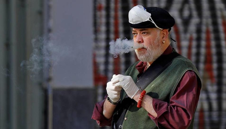 Un home es retira la mascareta per fumar una cigarreta.