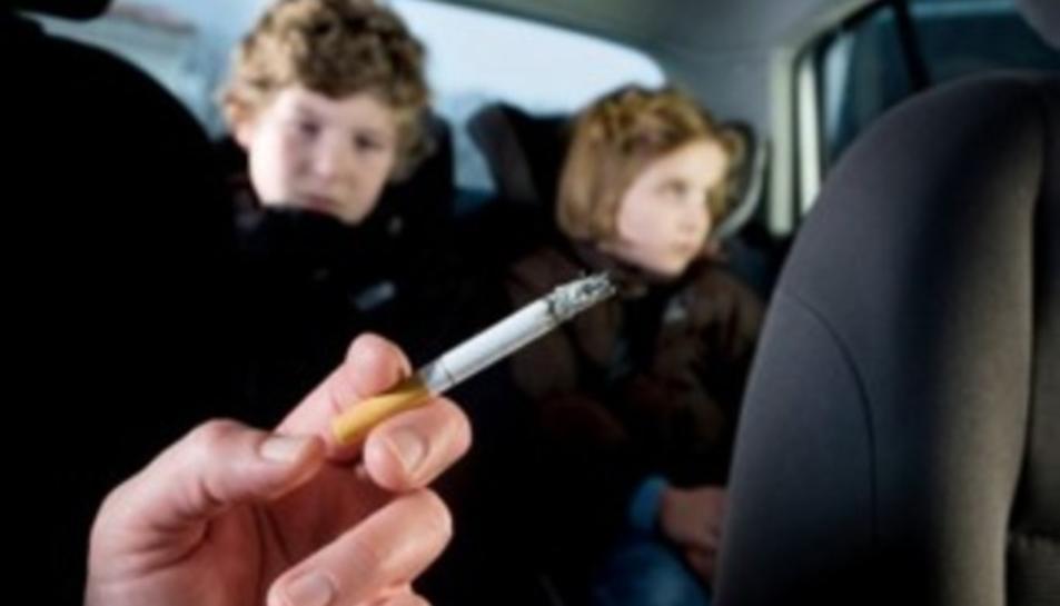 Un conductor fumant amb dos nens al darrera.