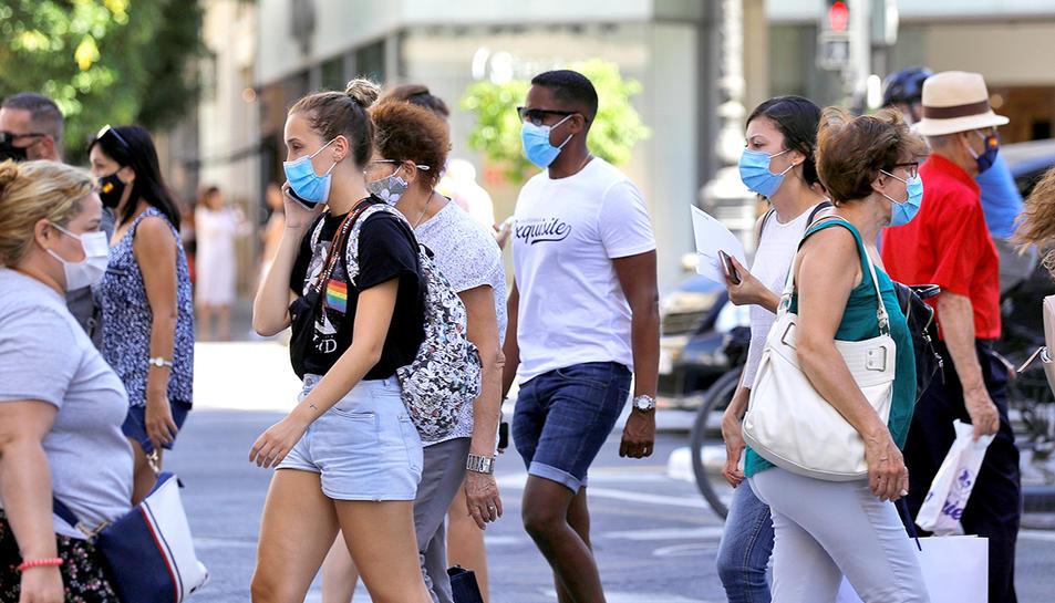 Diverses persones amb mascaretes en un pas de vianants.