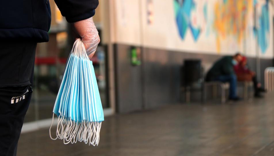 Una mà en primer pla sostenint un grapat de mascaretes a l'estació d'autobusos de Tarragona.