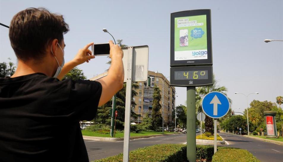 Un jove fotografia un termòmetre de carrer a Còrdova que marca 46 graus.