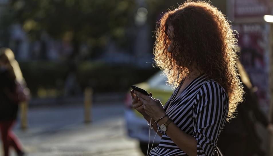 Una dona utilitzant el móbil al carrer.
