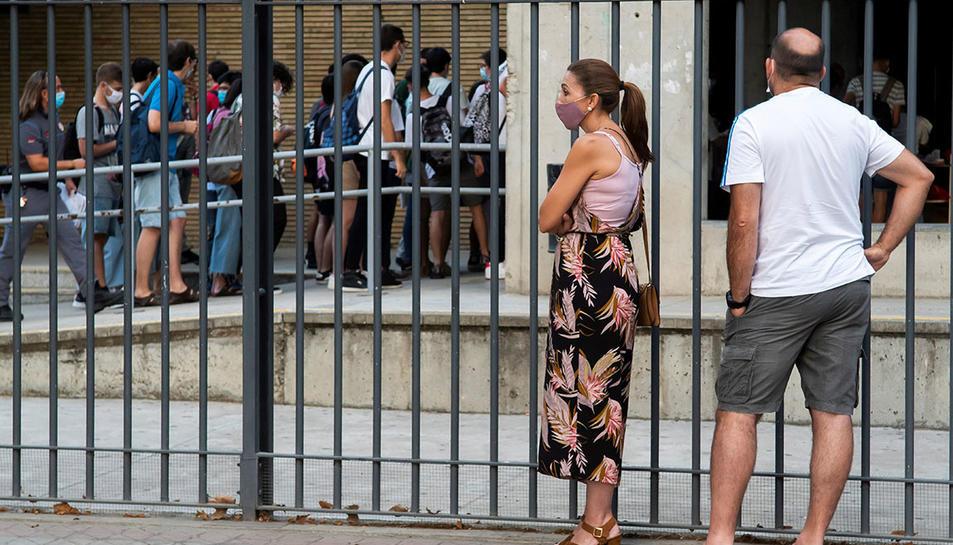 Una pares mirant com els alumnes accedeixen a un centre escolar.