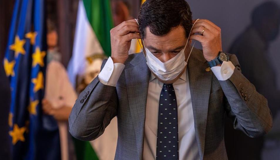 El president de la Junta d'Andalusia, Juanma Moreno, es col·loca una màscara després d'anunciar avui en Sevilla