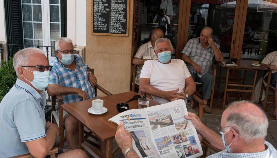Un grup de gent gran utilitzant mascareta en un bar.
