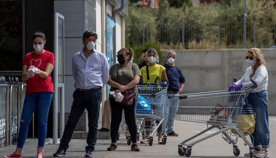 Diverses persones protegides amb mascaretes fan cua en l'entrada d'un supermercat.