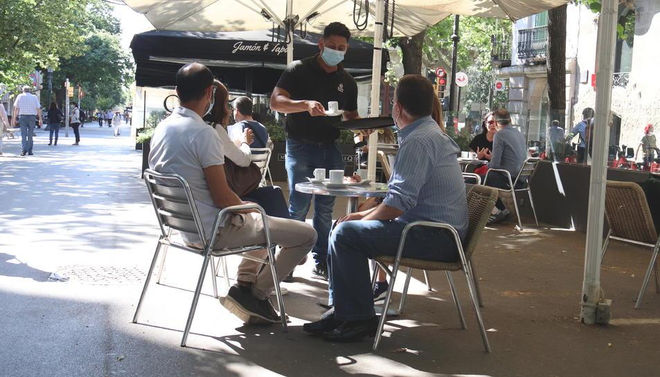 Un cambrer servint a la terrassa d'un bar a la la Rambla de Catalunya en el primer dia de fase 1 a Barcelona.