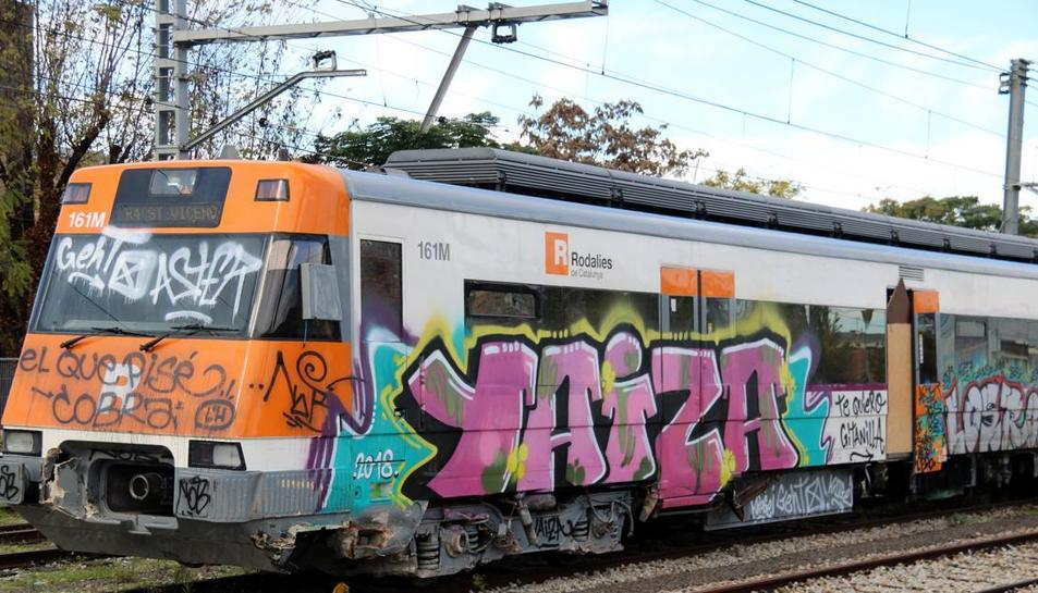Pla lateral de la capçalera del vagó d'un tren de Rodalies ple de pintades. // ACN - Gemma Aleman