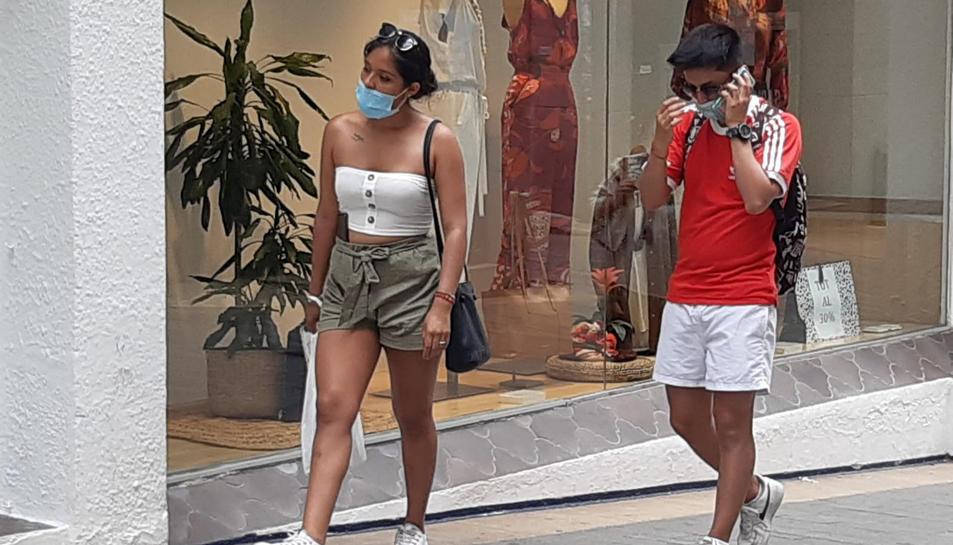 Pla general de dos joves amb mascareta passejant per Sitges.