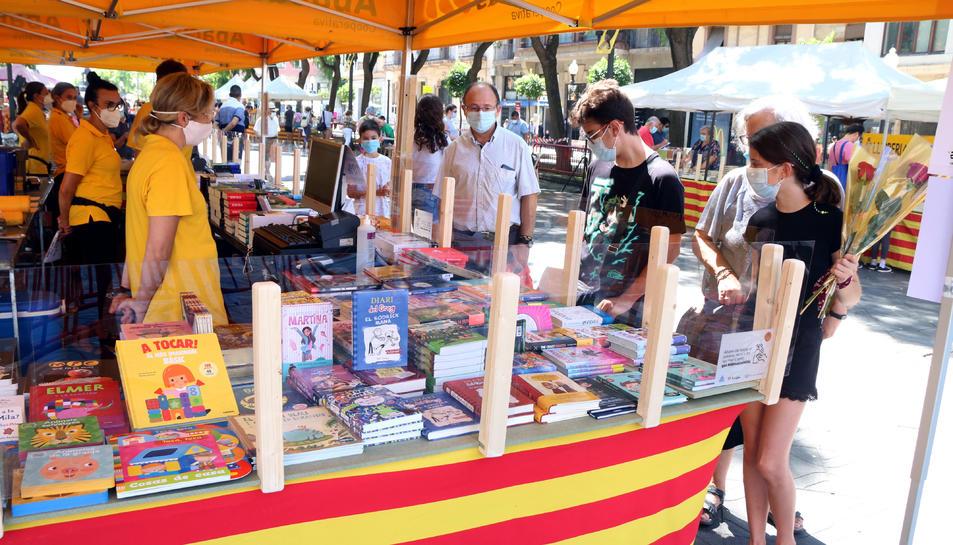 Una parada de llibres a la Rambla Nova de Tarragona amb diversos clients.