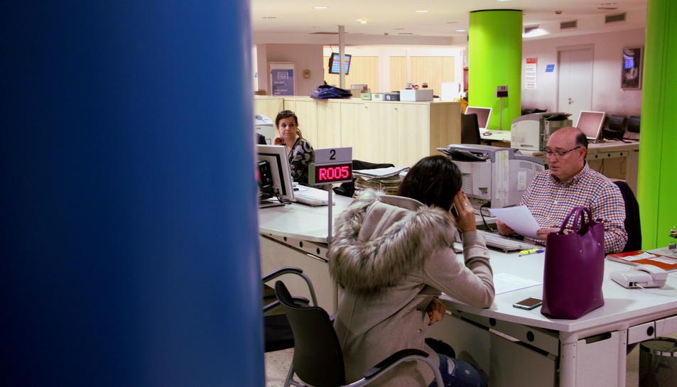 Una usuària del SOC sol·licita informació a un dels treballadors de l'Oficina del carrer Sepúlveda.