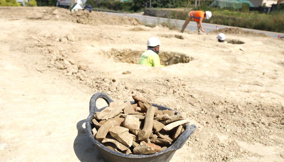 En primer pla, un cabàs amb ceràmiques recuperades a les sitges ibèriques de Serinyà