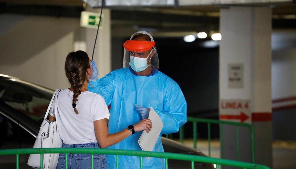 Personal sanitari agafant mostres er una prova PCR a una jove.
