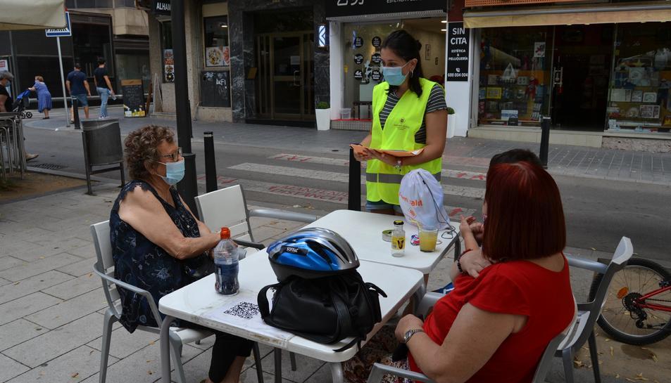 Una educadora informant a dues dones assegudes a una terrassa d'un bar de Reus.