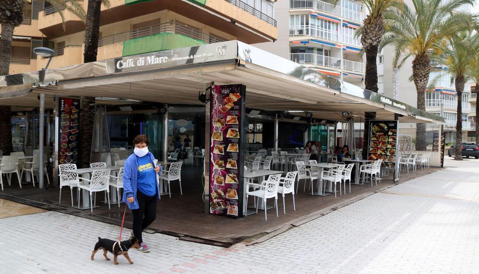 Pla obert d'una dona passejant un gos vora una terrassa del passeig de Salou pràcticament sense clients