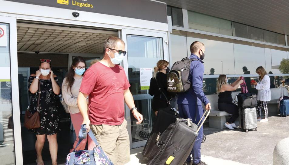 Pla general de turistes amb maletes, a la terminal d'arribades de l'aeroport de Reus.