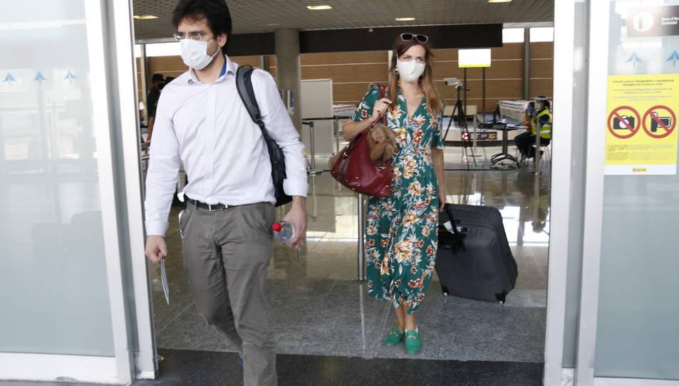 Dos passatgers amb mascareta, sortint del control de temperatura, a la terminal d'arribades de l'aeroport de Reus.