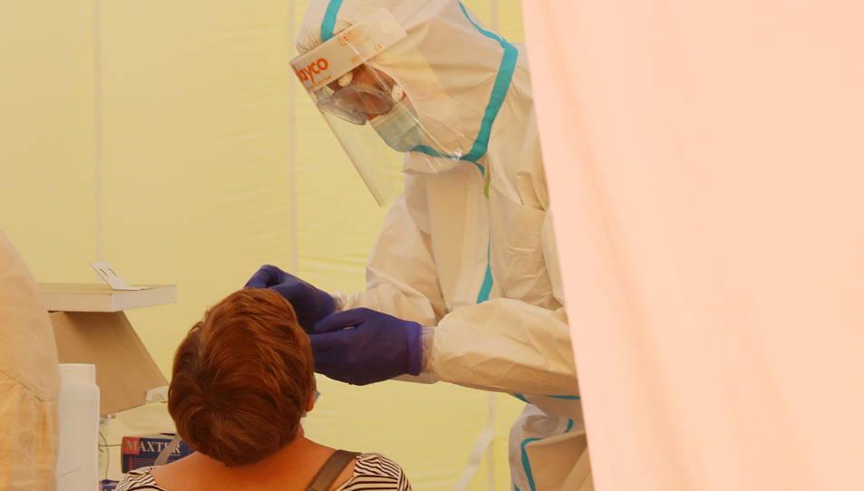 Un professional del CatSalut duent a terme una prova PCR a una veïna de Sabadell.