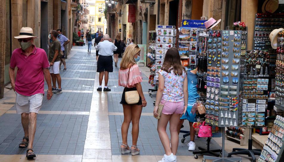 Una família de turistes mirant els expositors d'una botiga de records del carrer Major de Tarragona, el 28 de juliol.