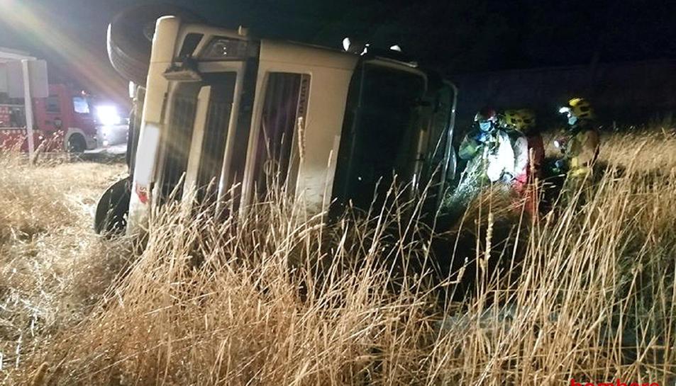 Els Bombers assistint el transportista que ha sortit de la calçada de l'AP-7 i ha acabat bolcant el camió la matinada