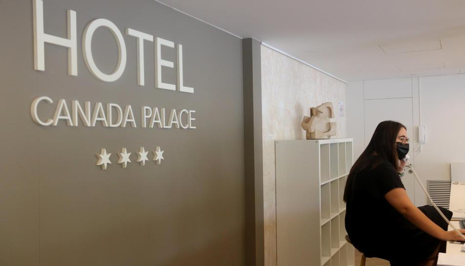 La recepció d'un hotel, amb una treballadora atenent el telèfon amb mascareta