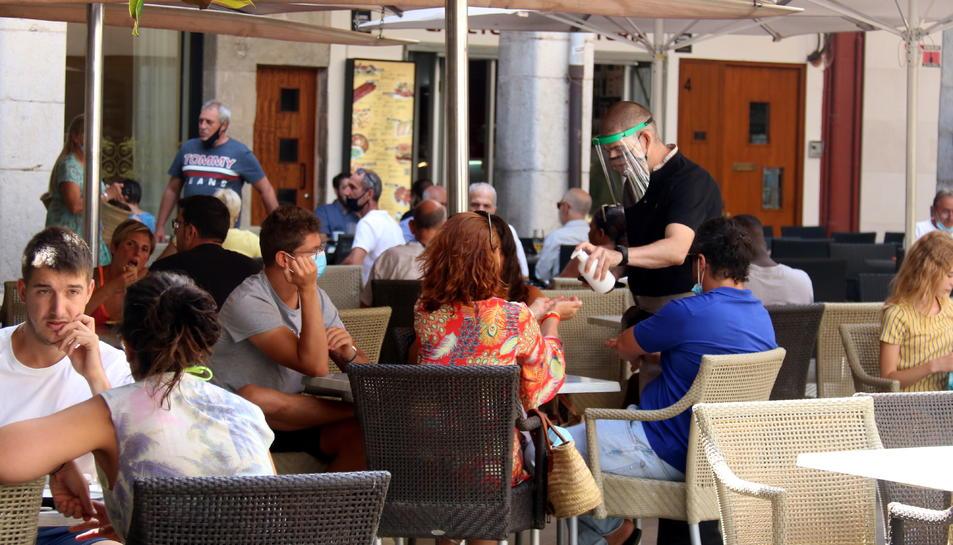 Un cambrer d'una terrassa de la plaça de l'Ajuntament posant hidrogel a uns clients.
