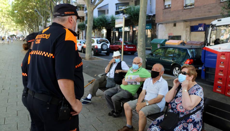 Dos voluntaris de Protecció Civil controlant l'ús de mascareta entre diversos veïns de Reus asseguts en un banc al passeig Sunyer.