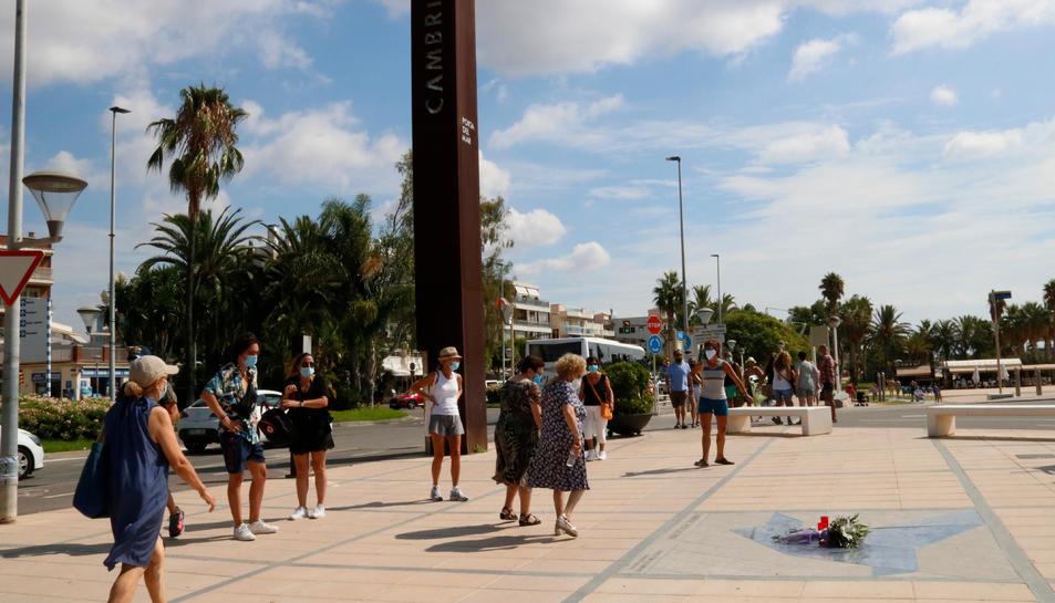 Turistes al passeig marítim de Cambrils, mirant encuriosits les flors i ciris al terra.