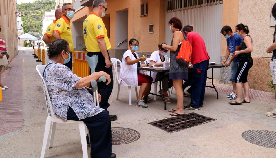 Pla obert de diversos veïns de Benifallet adreçant-se a una taula d'identificació per tal de realitzar-se una prova PCR.