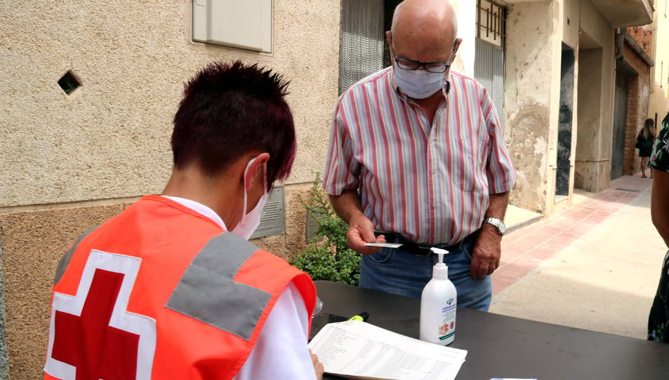 Un veí de Benifallet identificant-se davant un efectiu de la Creu Roja per tal de fer-se una PCR.