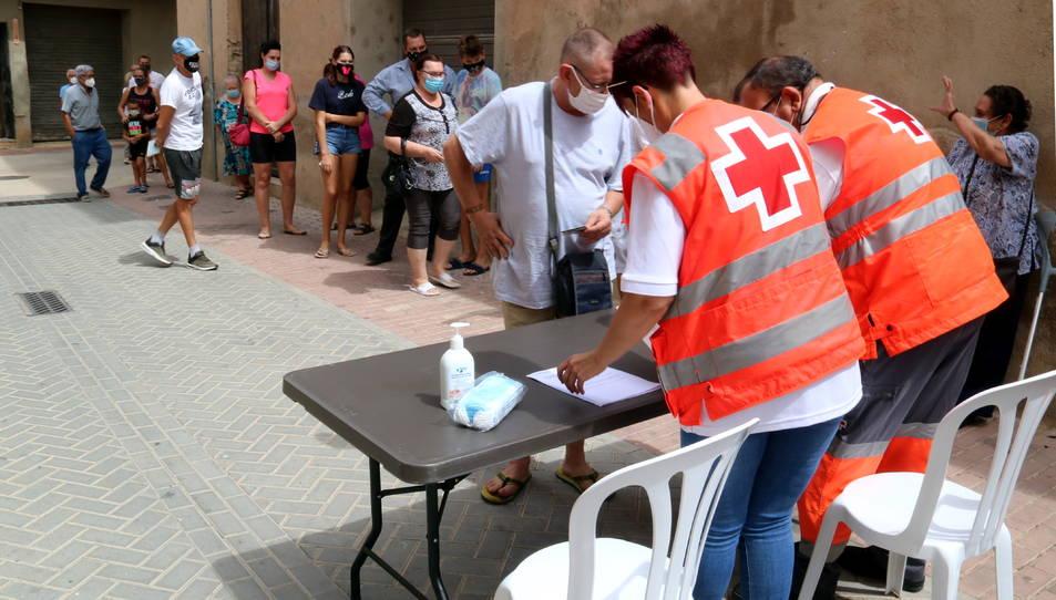 Pla obert de veïns de Benifallet fent cua davant un taulell d'inscripció per fer-se una prova PCR.