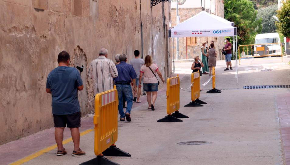 Una filera de veïns de Benifallet caminant cap al Casal Municipal, on es fa el cribratge massiu pel brot de covid-19 al municipi.