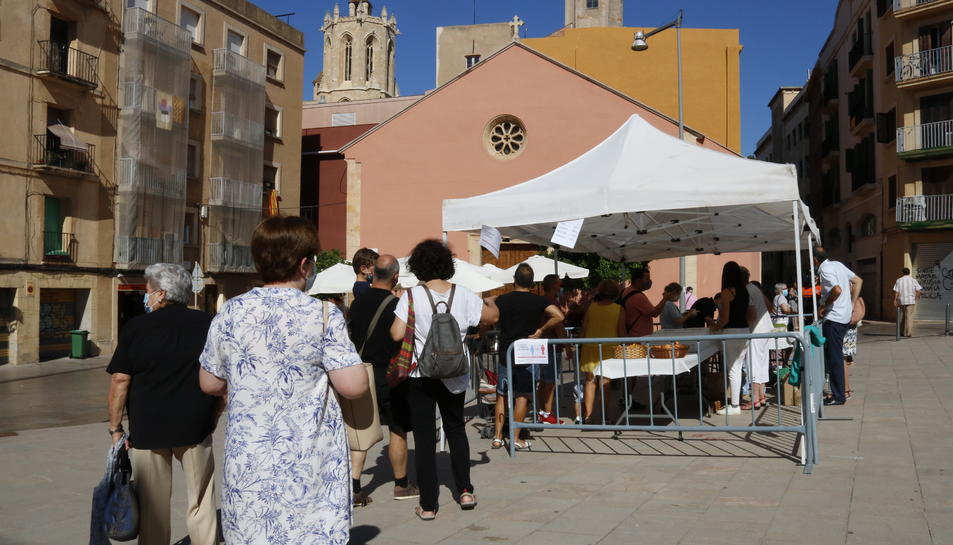 Una cua de persones en un punt de distribució d'aigua beneïda de Sant Magí, en un espai habilitat a la Part Alta.