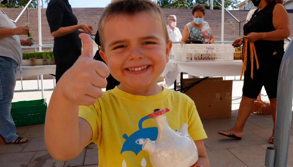 Un nen petit amb un càntir amb aigua de Sant Magí, aixecant el dit polze en senyal que tot va bé, en un espai habilitat a la Part Alta
