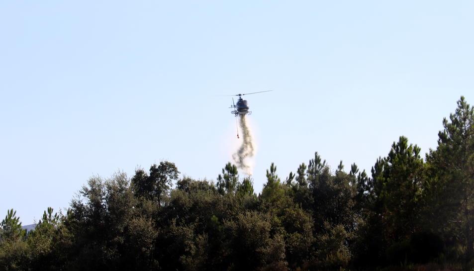 Un helicòpter sobrevolant la zona afectada per l'incendi forestal.