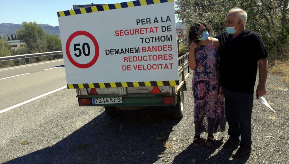 Pla general de dos dels veïns de la nova plataforma d'Ascó al costat del cartell reivindicatiu per demanar millores en seguretat viaria a la C-12