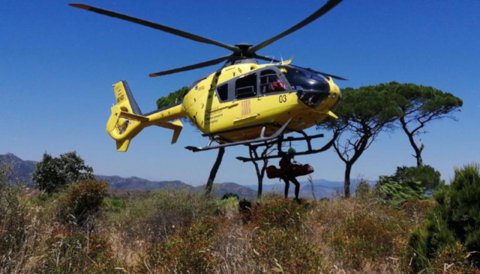Un Bomber dels GRAE amb la llitera carregant l'home a l'helicòpter del SEM