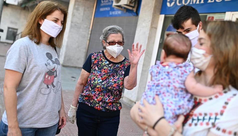 Un grup de persones amb mascaretes se saluden al carrer.
