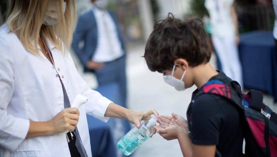 Un nen es desinfecta les mans després que li prenguin la temperatura a l'entrada del col·legi privat internacional American School of Barcelona.