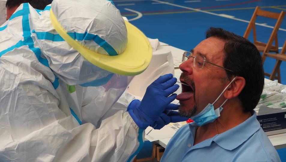 Pla detall d'un home fent-se la PCR amb un tècnic sanitari a Sant Joan de les Abadesses.