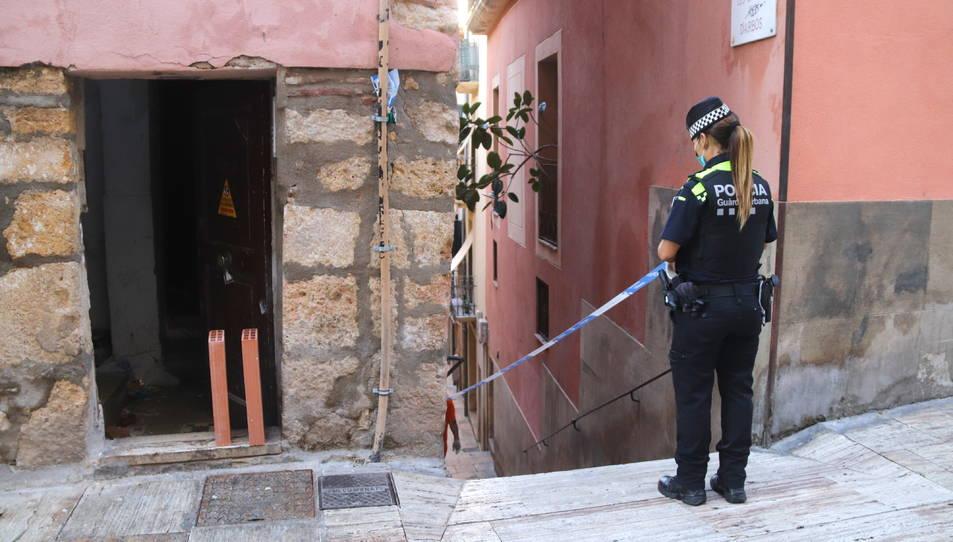 Una agent de la Guàrdia Urbana precintant l'entrada de l'edifici desallotjat a la Part Alta de Tarragona.