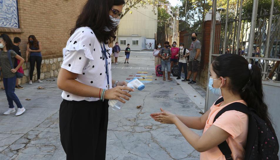Una docent pren la temperatura i aplica gel a una alumna de l'Escola Prat de la Riba de Reus.