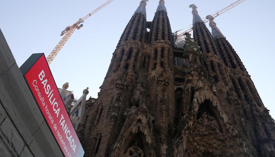 Façana de la Sagrada Família amb un cartell que informa que el temple roman tancat (entre setmana).