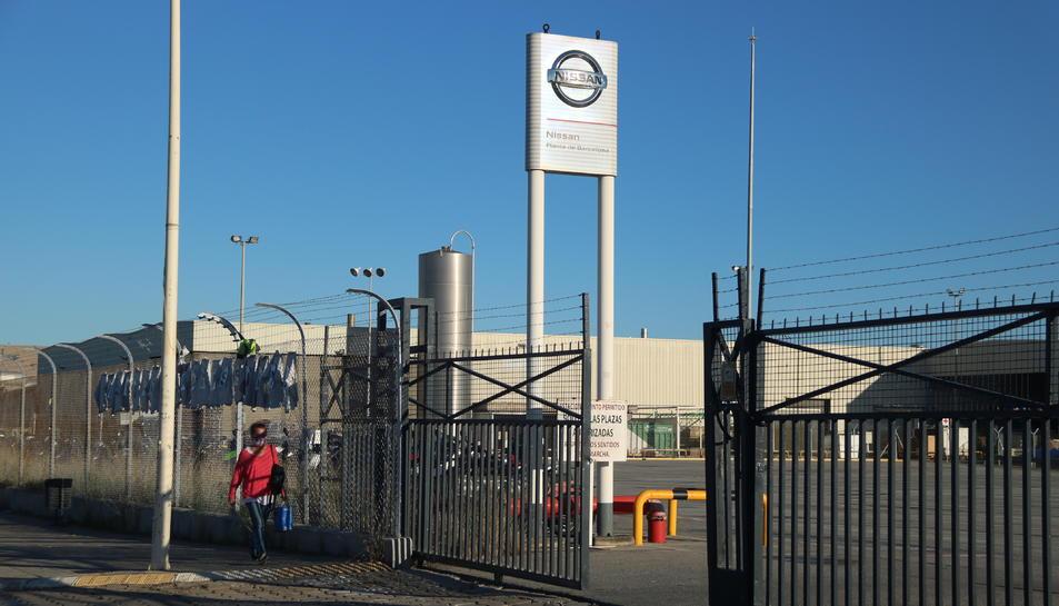 Una treballadora de Nissan davant l'entrada de la planta de la Zona Franca durant el primer dia en què s'ha reprès la producció de vehicles a la fàbrica