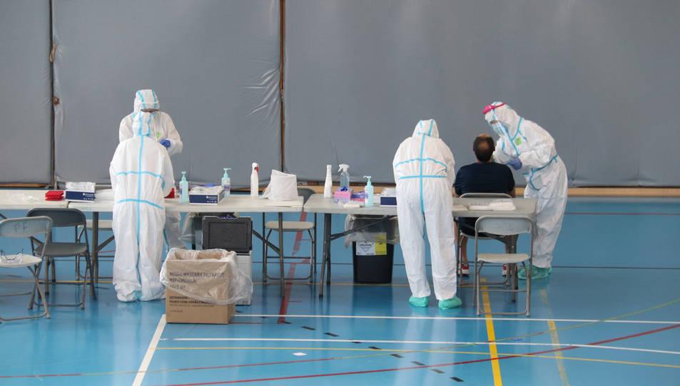 Alguns sanitaris fent proves PCR a un gironí en el primer dia de cribratges massius a Santa Eugènia.