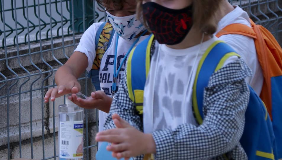 Dos alumnes de primària rentant-se les mans amb gel hidroalcohòlic a l'accés de l'escola Sant Llàtzer de Tortosa.